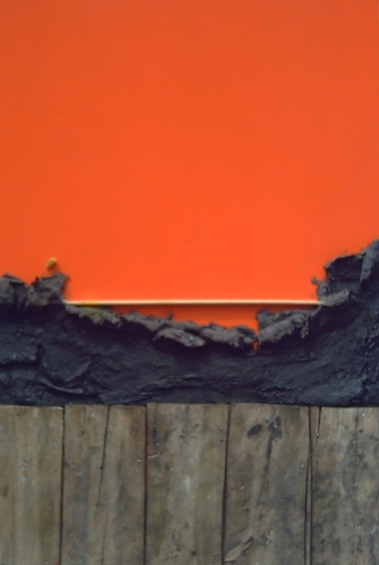 Work with black reliefs protruding above an old wood fence with orange background